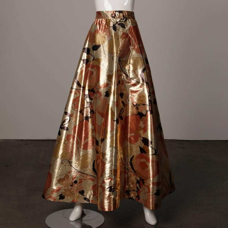 Stunning vintage 1970s 2-piece evening dress ensemble by Arnold Scaasi in metallic gold printed silk lamé. This ensemble fits like a modern size XS. The top is fully lined with rear zip and hook closure. Boning in back. The bust measures 32
