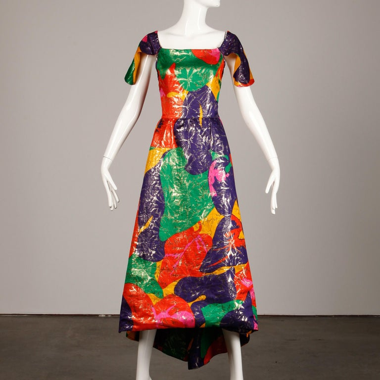 Incredible vintage metallic lame dress by Arnold Scaasi with a high low hemline and open back with chain detail. Petal shaped flap sleeves and tropical-inspired floral printed colorful silk fabric. Fully lined with rear zip and hook closure. Hidden