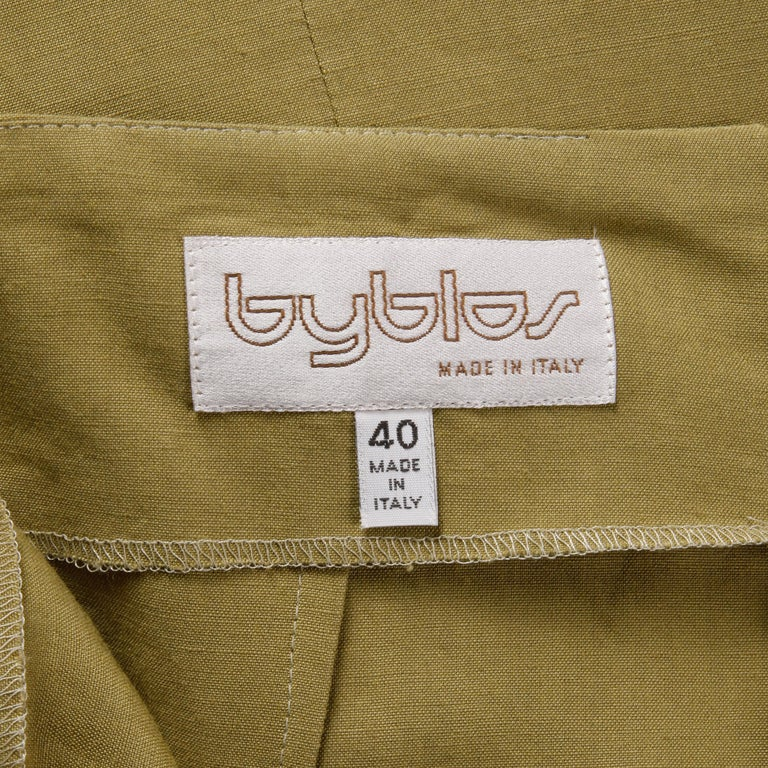 Flattering vintage olive green 1990s asymmetric skirt by Byblos in what feels like a stretch linen fabric. Unlined with rear zip closure. The marked size is 40, and the skirt fits like a modern size small. The waist measures 26