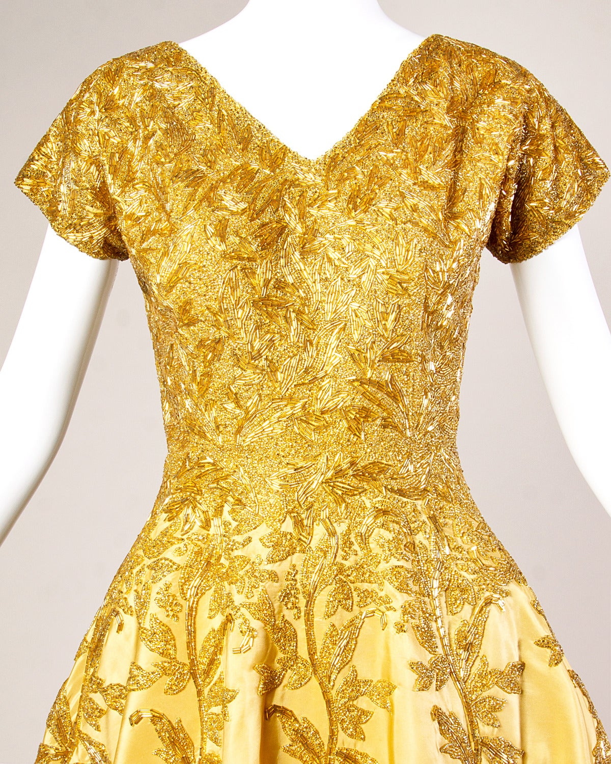 Absolutely one of the most stunning dresses we have ever laid eyes on! This dress is just incredible. Gorgeous gold-yellow silk cocktail dress with heavy hand beaded design. Full sweep, short sleeves and V-neck. 