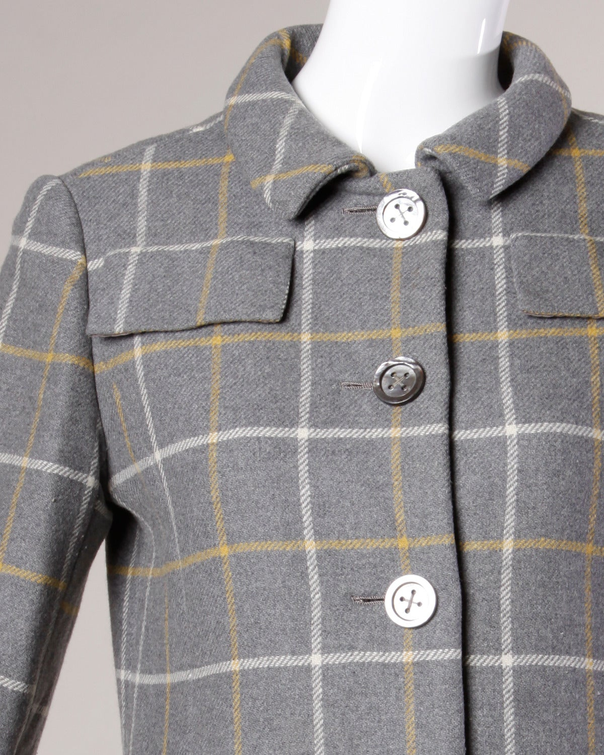 Beautifully tailored wool jacket with heavy shell buttons and flap pockets by Christian Dior.  Details:  Fully Lined Shell Buttons Fabric: Wool Estimated Size: Medium Label: Christian Dior New York Colors: Gray/ Yellow/