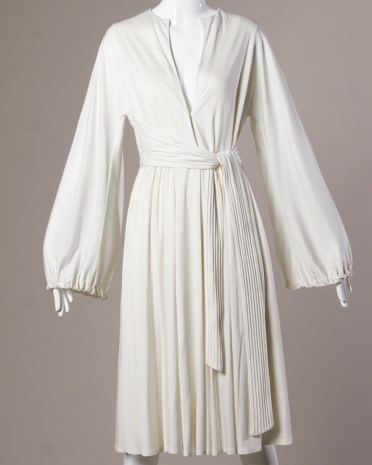 Gorgeous vintage white jersey midi dress by Donald Brooks. Plunging neckline can be snapped up for a more modest look. Full blouson sleeves and attached waist sash.