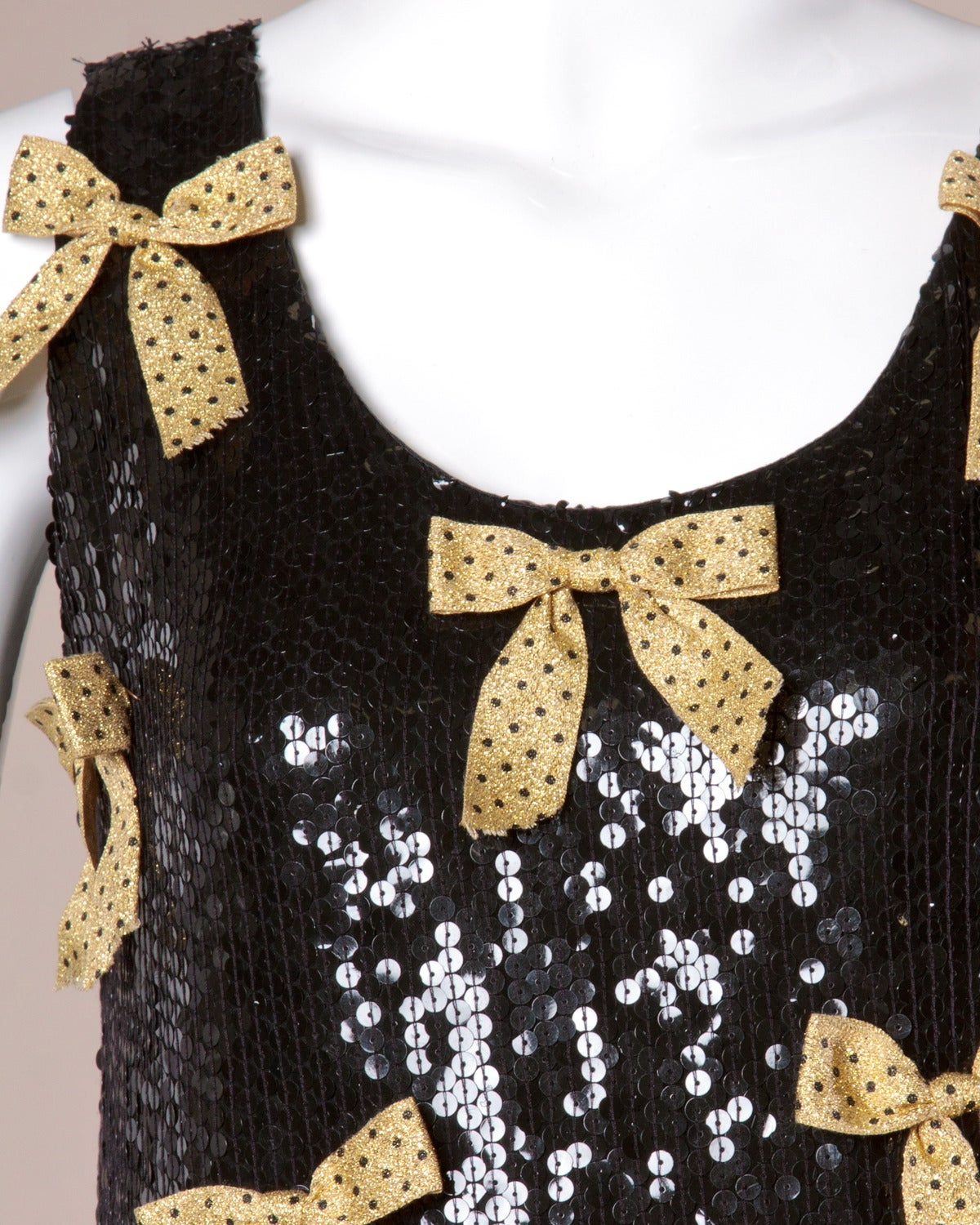 Jeanette Kastenberg for St. Martin vintage black sequin shift dress with metallic gold bow appliques on the front of the dress.   Details:  Fully Lined Side Zip and Hook Closure Marked Size: M Estimated Size: S-M Label: Jeanette for St.
