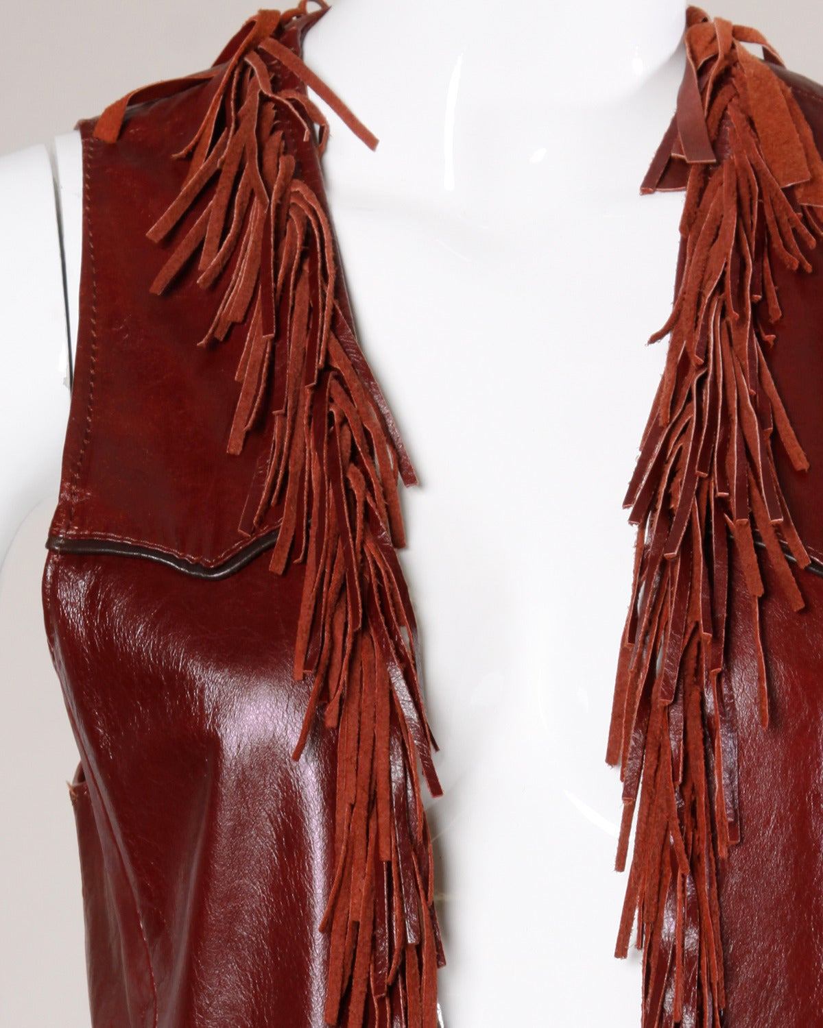 "Vintage oxblood leather vest with fringe trim by Char. This Char vest has a ""Char & Sher Designs"" label from the eight year period in which Charlotte Blankenship de Vasquez partnered with her sister Sherry Stein from 1982-1990. Silver buffalo coin"