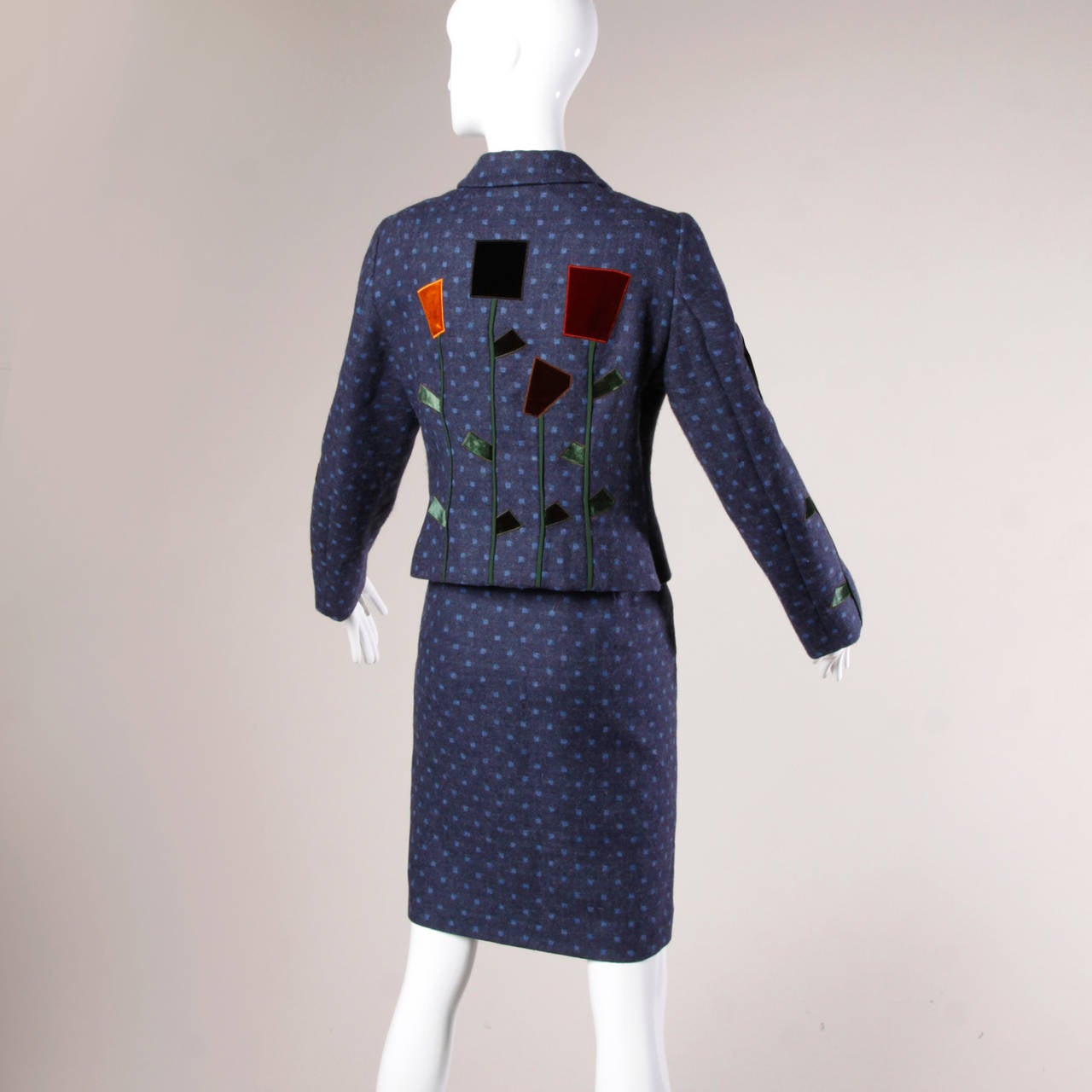 Vintage Moschino blue polka dot skirt suit with patchwork flower design.  Details:  Fully Lined Shoulder Pads Sewn Into Lining Button Closure On Jacket/ Side Zip and Hook Closure On Skirt Marked Size: I 46/ US 12/ D 42/ F 42/ GB 14 Color: