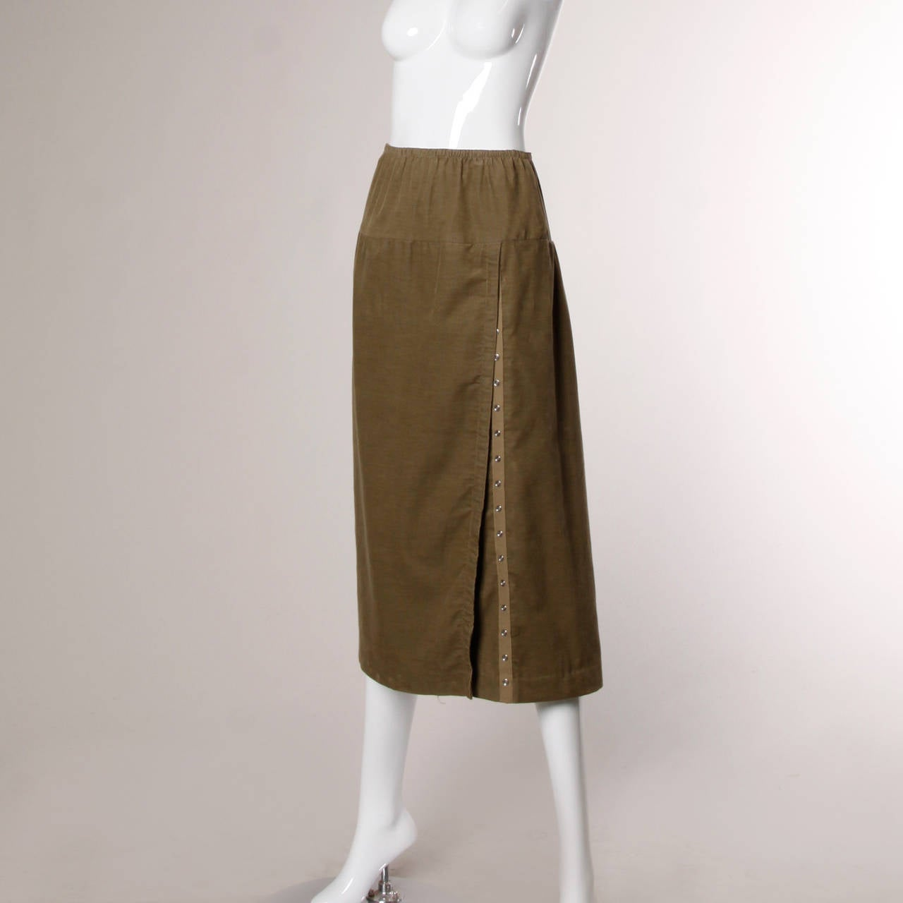 So avant garde and so Norma Kamali! This asymmetrical skirt features snap up detailing and light weight olive green corduroy.
