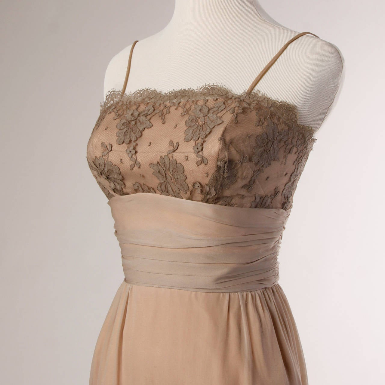 Elegant vintage cocktail dress by California designer Edith Flagg. Nude silk with chantilly lace bustline.  Details:  Fully Lined Back Metal Zip and Hook Closure Marked Size: Not Marked Color: Deep Gray Taupe/ Creamy Peach Beige Fabric:
