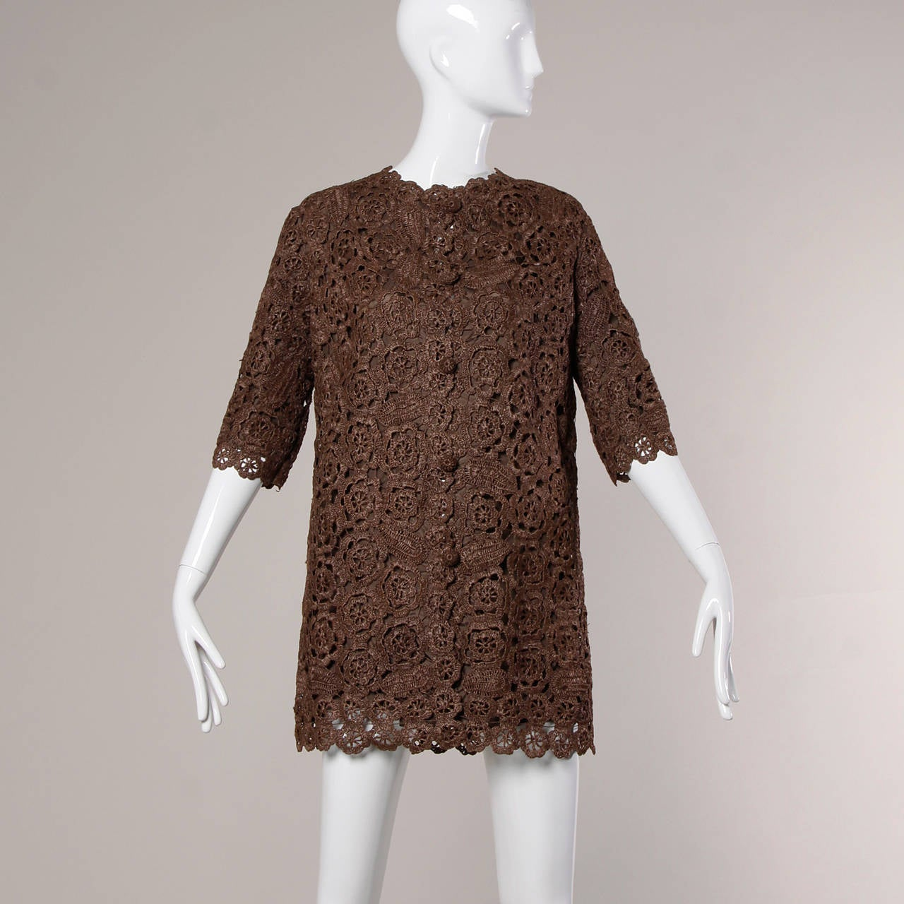 Hand crocheted brown raffia coat or jacket with a scalloped design and matching buttons.