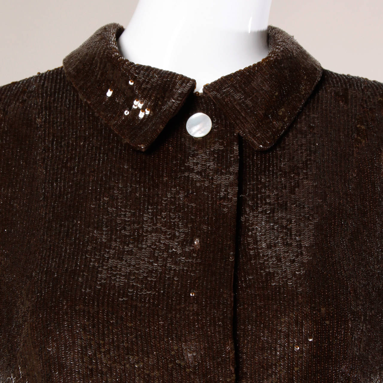 Chocolate brown silk short sleeved top or jacket encrusted in tiny sequins by Oscar de la Renta. Satin lining and two decorative pearl buttons.
