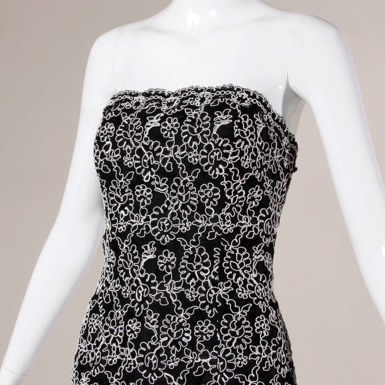 Vintage black lace cocktail dress with white tambour embroidery by Bill Blass.   Details:  Fully Lined Back Zip and Hook Closure Strapless Marked Size: 6 Estimated Size: S-M Color: Black/ White Fabric: Polyester Shell/ Rayon Lining Label: