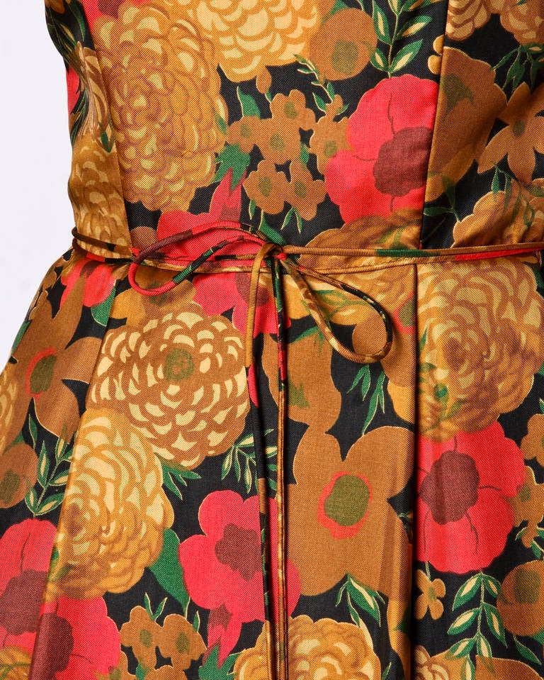 Gorgeous creamy silk cocktail dress in an autumn colored floral print. Full sweep, 3/4 length sleeves and a waist tie. Rear metal zip closure.