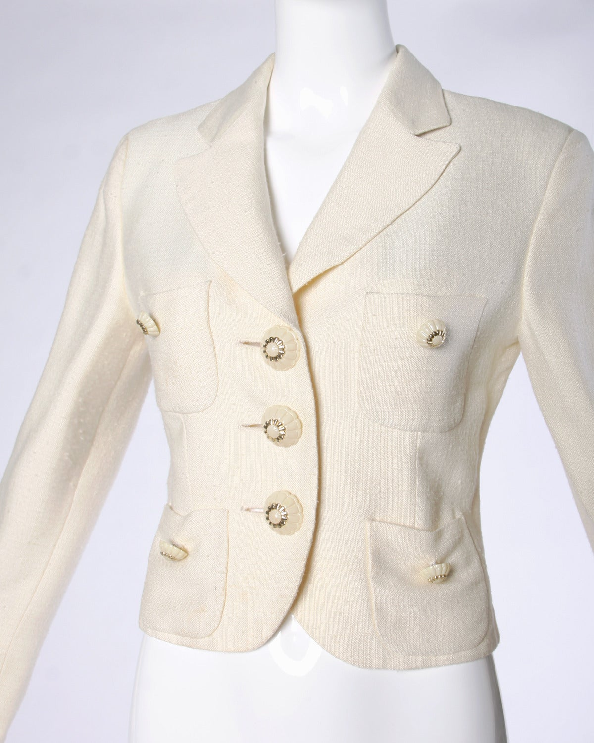 Gorgeous cream jacket with unique buttons and front pockets. By Moschino Couture!  Details:   Fully Lined Front Pockets Shoulder Pads Sewn Into Lining Front Button Closure/ Button Closure At Wrist Marked Size: I 42/ D 38/ F 38/ GB 10/ US