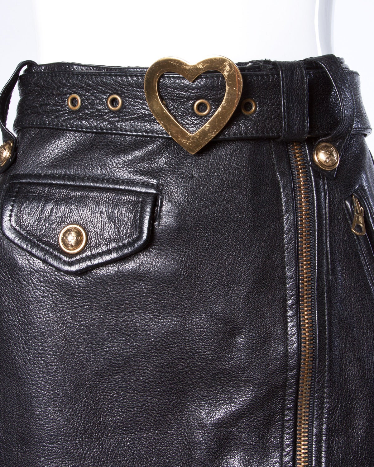 """Vintage black leather pencil skirt by Moschino. This skirt features an asymmetric zipper, """"Cheap & Chic"""" logo buttons and a heart buckle on the attached belt.   Details:  Fully Lined Front Pockets/ Side Pockets Matching Belt Attached Front"""