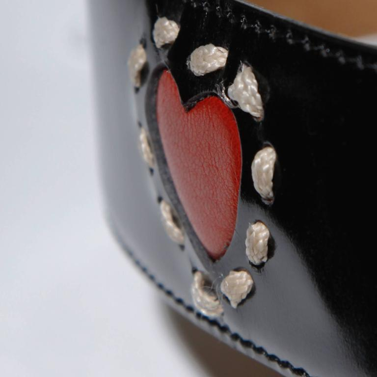 Moschino by Redwall vintage black leather belt with red hearts and a big gold tone heart buckle. Decorative stitching. Estimated size large.