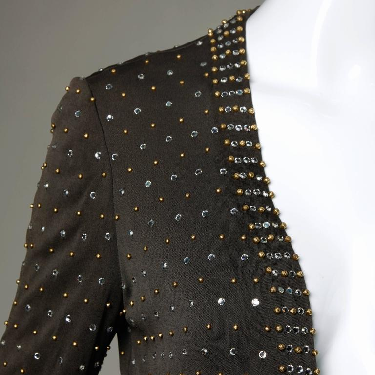 Stunning heavily beaded and rhinestone embellished silk jersey jacket by Adele Simpson. Heavy crystal rhinestones and hand beadwork!  Details:  Fully Lined Marked Size: Not Marked Estimated Size: S-M Color: Dark Taupe/ Gold/ Crystal  Fabric: