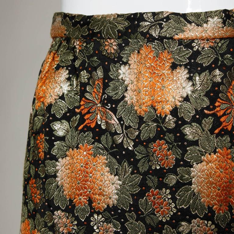 Metallic brocade vintage 1960s maxi skirt with a back slit.   Details:  Fully Lined Side Zip and Hook Closure Marked Size: Not Marked Estimated Size: S-M Color: Black/ Gold Metallic/ Orange/ Olive Green/ Light Orange Fabric: Metallic