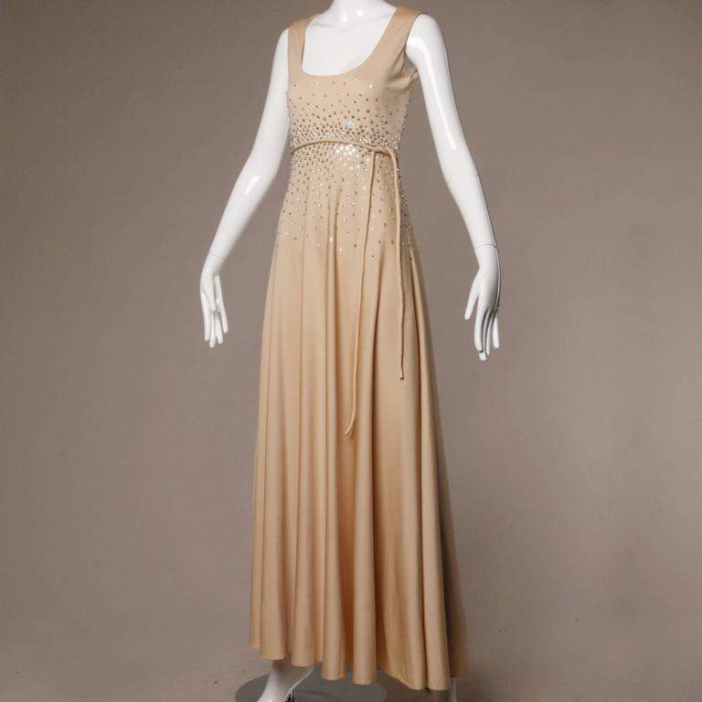 Stunning vintage nude jersey knit maxi dress with an empire waist and silver sequins.   Details:  Fully Lined Matching Belt Back Metal Zip and Hook Closure Marked Size: Not Marked Estimated Size: S-M Color: Beige/ Silver Metallic  Fabric: