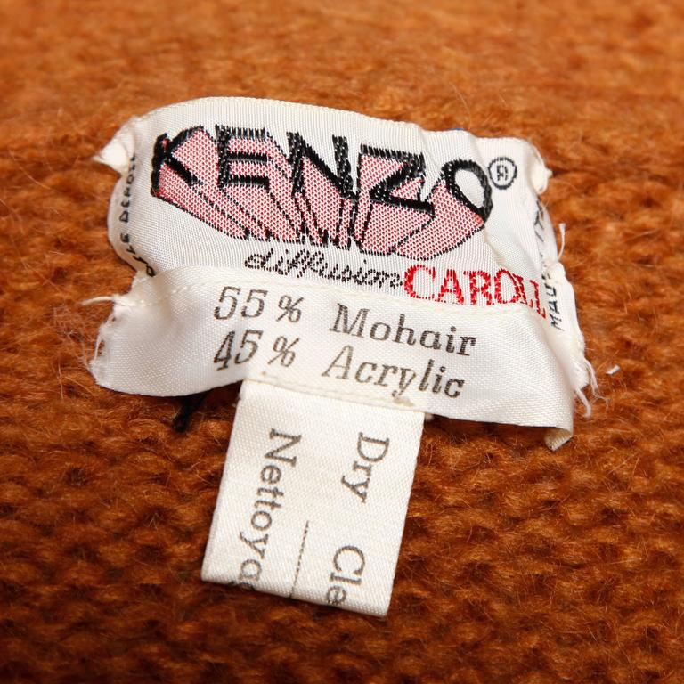 Amazing vintage chunky knit cocoon jacket by Kenzo. Fringe trim and matching waist sash tie.  Details:   Unlined Front Pockets Sash Tie Closure Marked Size: Not Marked Estimated Size: Free Color: Camel Fabric: 55% Mohair/ 45%