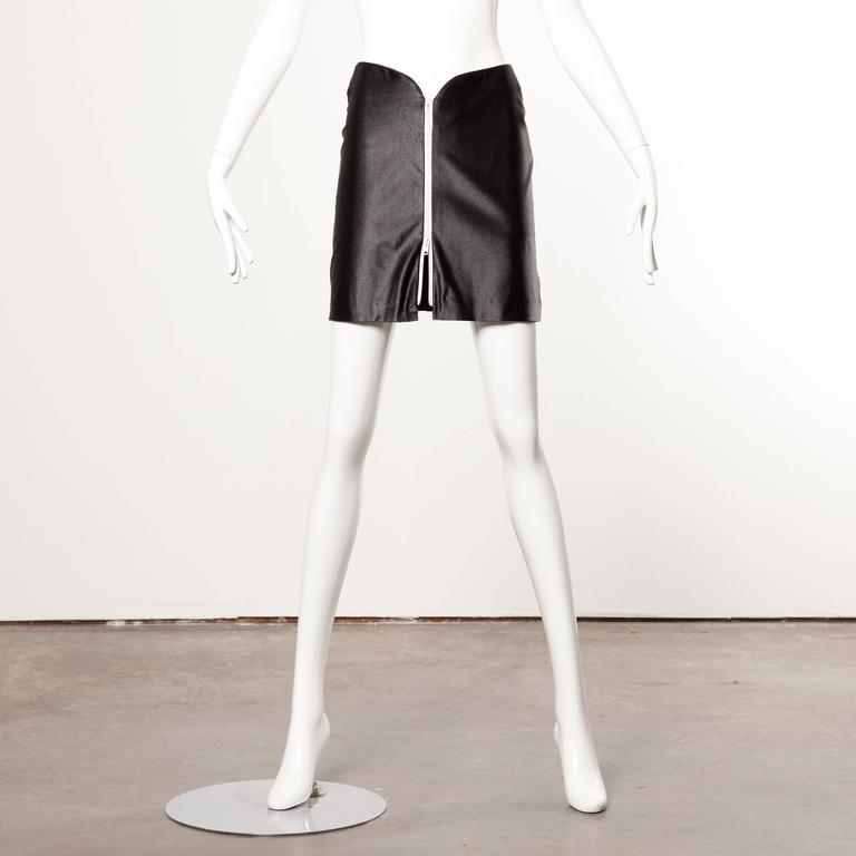 Iconic 1970s vintage shiny wet look disco zip up mini skirt by Le Gambi.  Details:   Unlined Zip Front Closure Marked Size: 9/10 Estimated Size: Small Color: Black/ White Fabric: 85% Nylon/ 15% Lycra Label: Le Gambi  Measurements: