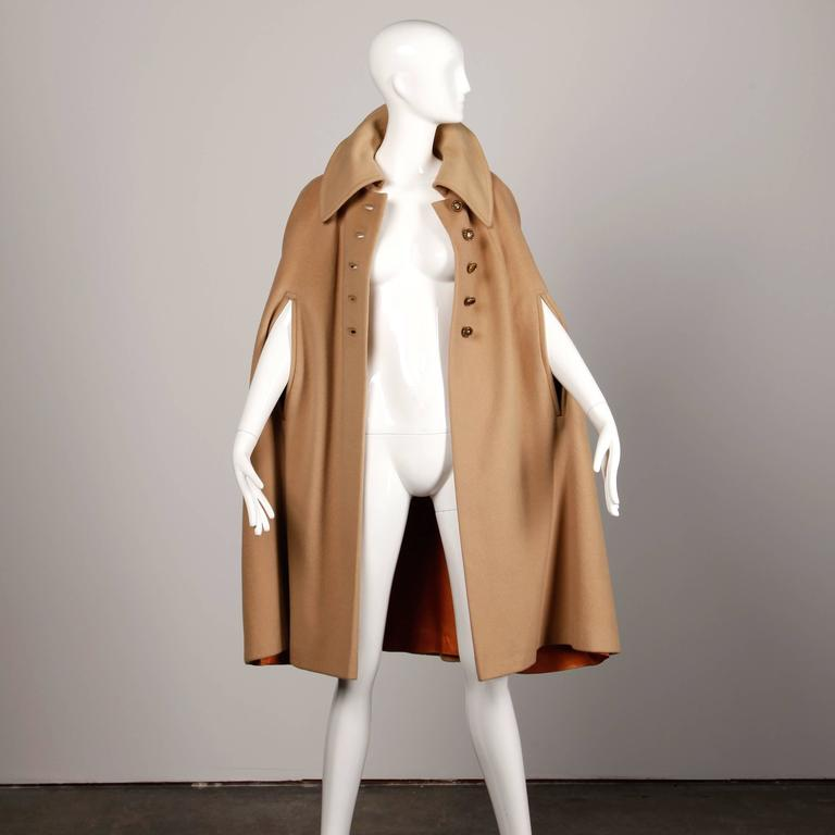 Chic vintage 1970s camel wool cape coat with oversized collar and arm slits.  Details:   Fully Lined Button Front Closure Marked Size: Unmarked Estimated Size: Free (S-L Color: Camel Fabric: Wool Label: Youthcraft  Measurement:  Total