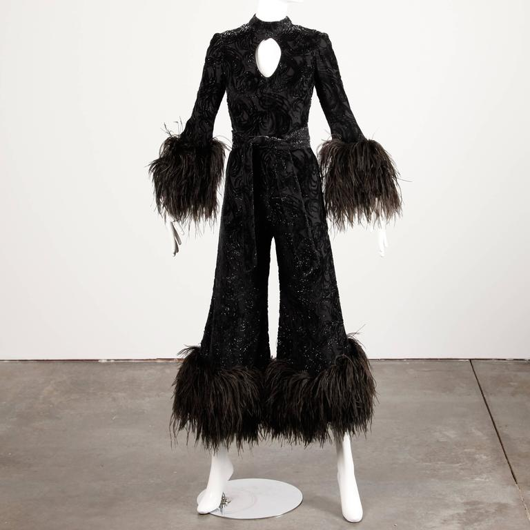 Show stopping vintage 1970s black burnout velvet jumpsuit with massive ostrich feather cuffs and a cut out keyhole neckline by Lillie Rubin. Fabric is textured with flecks of metallic. There is a matching sash that ties around the waist and is not