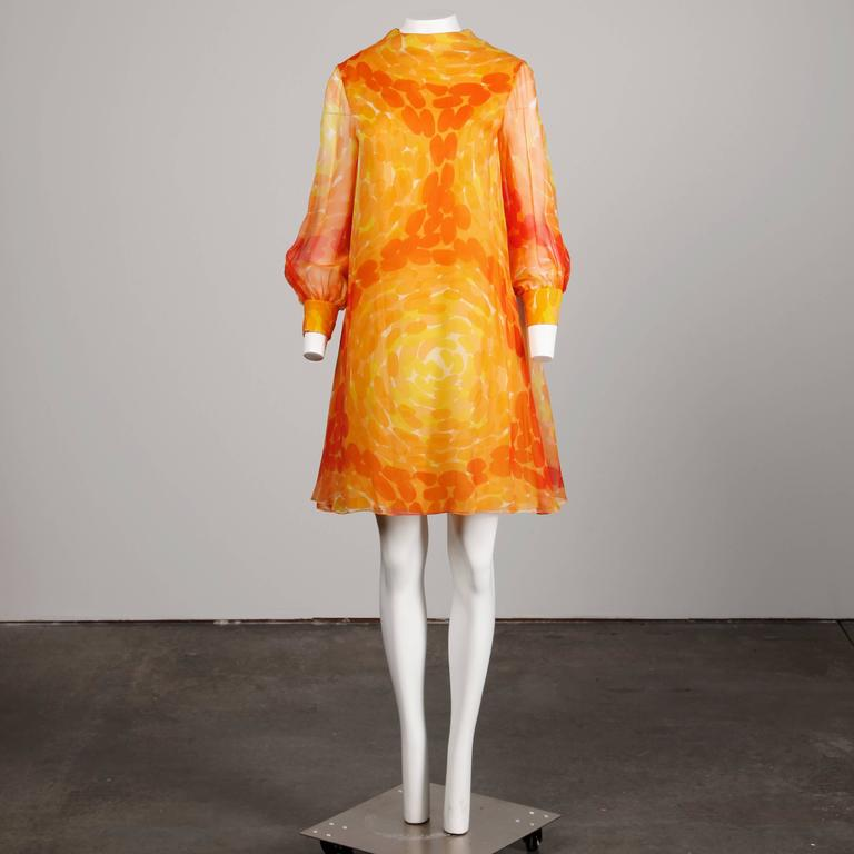 Amazing 1960s vintage screen printed mod dress by Pab. Long sheer sleeves and vibrant print in orange and yellow.