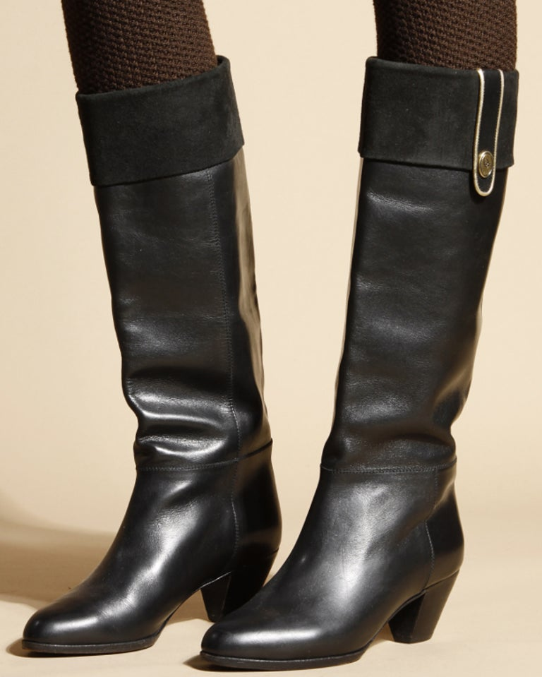 Black leather riding boots by Christian Dior. All lined with beige leather lining. Christian Dior logo on the interior in gold embossed letters. Finished with suede cuffs and a tiny Dior brass logo on the side. Marked size 5. Stacked wooden heel.