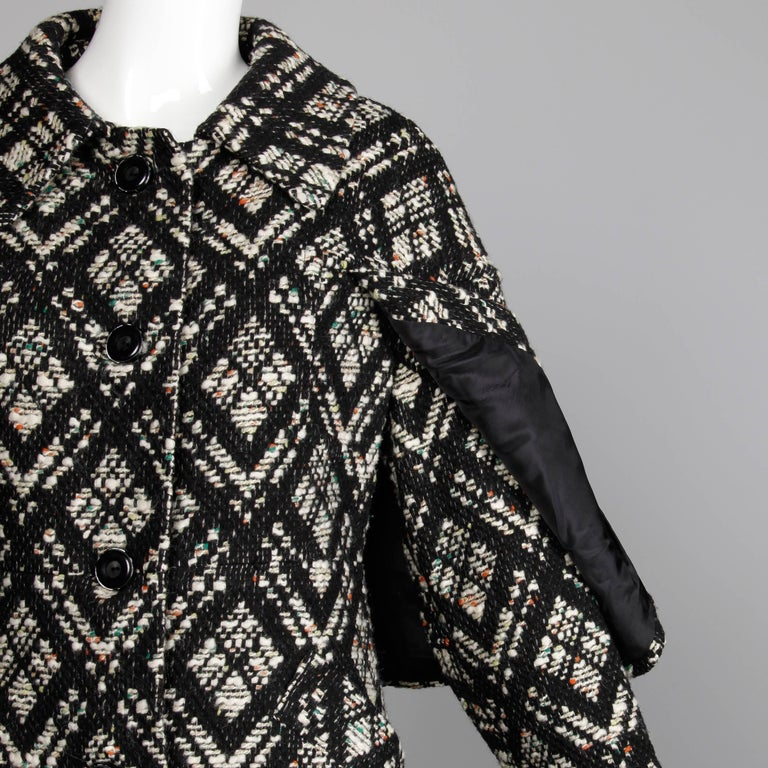 Darling vintage 1970s black and white Irish wool coat with attached cape detail and black fringe trim. Fully lined with front button closure. Front pockets. Fits like a modern size small. The bust measures 36