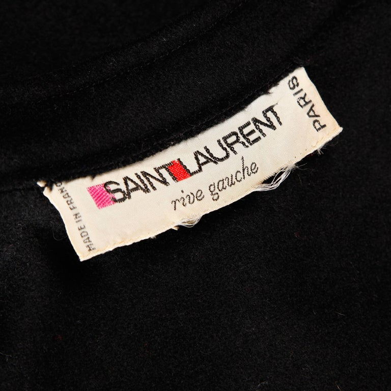 Completely amazing vintage heavy black wool cape coat by Yves Saint Laurent from the 1970s. The cape features two layers with giant bat wing sleeves and front button closure. Long maxi length. Early Yves Saint Laurent Rive Gauche label. Fits most