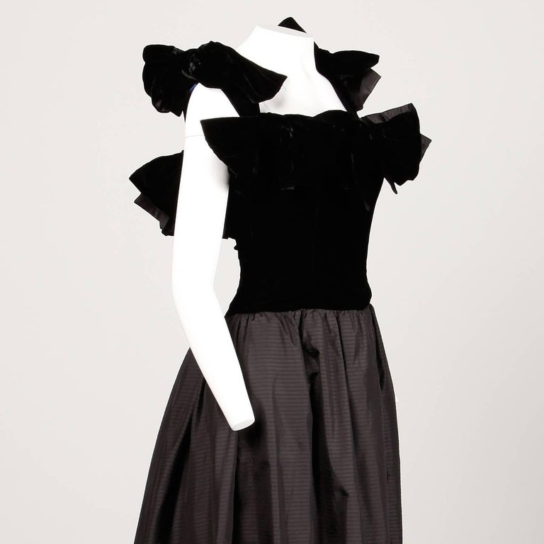 Fantastic 1980s black silk evening gown by Lanvin. Giant velvet avant garde bows and full silk back train. Built in tulle crinoline and double zip side closure. Fully lined with side zip and hook closure. The marked size is 40, but the dress fits