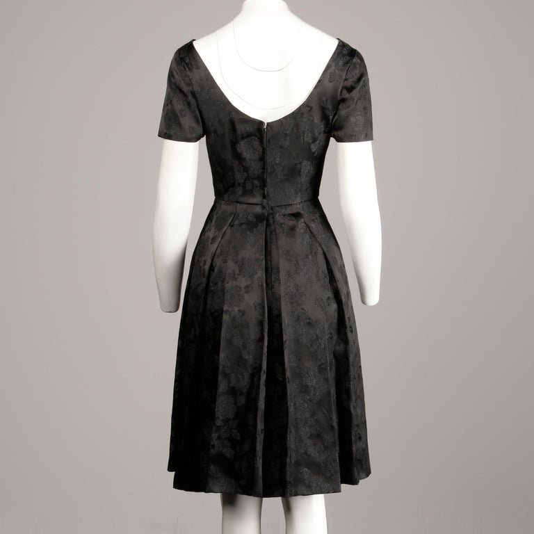 Simple and chic 1960s vintage cocktail dress with short sleeves and box pleats. Partially lined with rear metal zip and hook closure. Fits like a modern size small. The bust measures 38