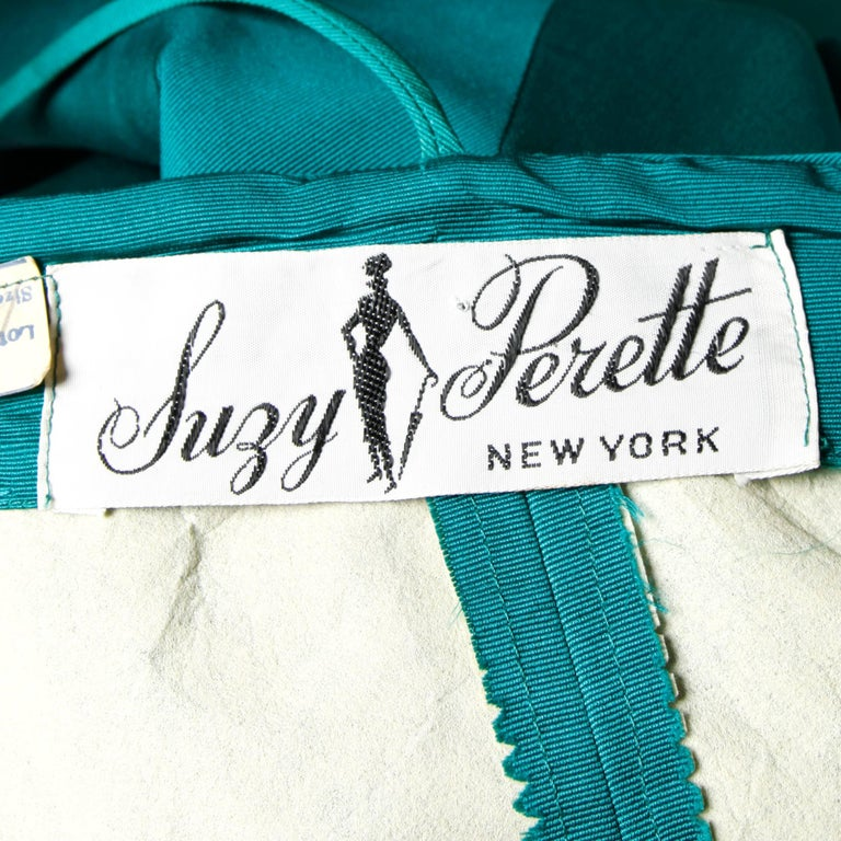 Stunning and unique emerald green silk taffeta dress with an origami bubble hem by Suzy Perette. Bow detail at the bottom and hourglass silhouette. Fits like a modern size small. Please see measurements below.  Details:  Unlined Back Metal Zip and