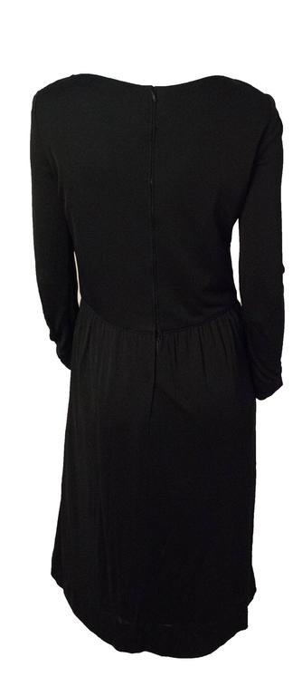 70s Ceil Chapman black silk jersey dress. Lace up front. Rhinestone encrusted grommets and end pieces on lace. Metal zip up the back. Fully lined.