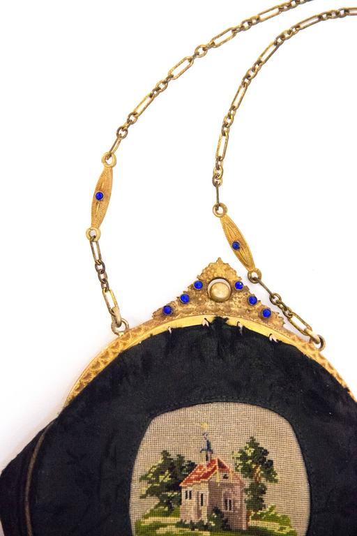 Edwardian black jacquard pouch purse with petit point scene of a house and trees. Gold toned metal frame with blue glass embellishments. Original interior small round mirror that is attached with a small chain. Roughly lined in cream colored cotton.
