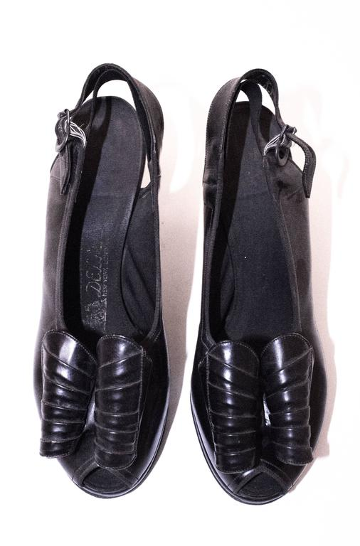 40s Black Slingback Heel with Oversized Bow.  Measures 9 inches long from toe to heel. Palm of foot measures 3 inches wide. 2 inch heel.