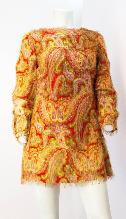 60s Paisley Print Novelty Fabric Mini Dress with Cutout Sleeves. 3 matching fabric covered buttons along each sleeve. Metal zipper up the back.