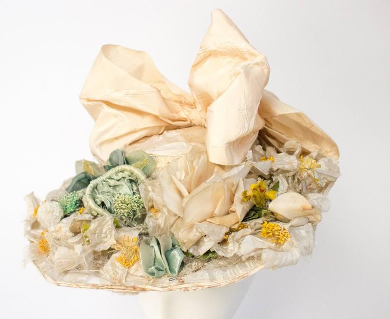 1910s Floral Edwardian Hat w/ Large Bow. Genuine white Edwardian hat w/ silk flowers and white jacquard bow with bird motif.