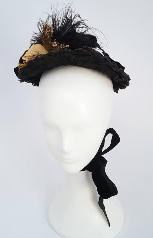 Black Victorian Bonnet w/ Beads & Feathers. Lace underside of brim. Velvet bows and jet beads on back. Feathers and flowers on brim. Silk ribbon ties.