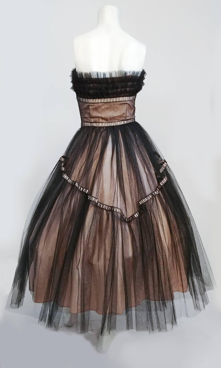 1950s Emma Domb Black and Pink Tulle Party Dress. Ruffled tulle bodice embellished with pearls. Ribbon embellishments. Two layers of black tulle over pink lining. Boned bodice. Worn over large petticoat in photo for full effect.