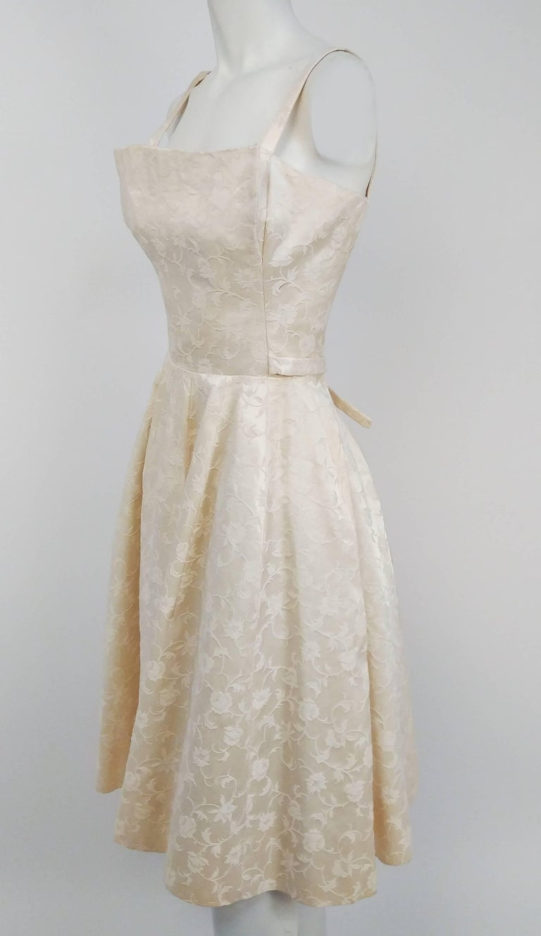 1950s White Jacquard Cocktail Dress. Interesting origami bodice design. Ties at waist at back. Built in tulle petticoat.