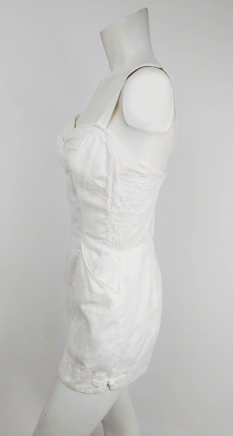 1950s Kamehameha White Cotton Damask Romper. Two front pockets. Frog clasp detail at side leg seams. Zips up back. Side panel shirring. Built-in cups in lining for support. Adjustable back straps.