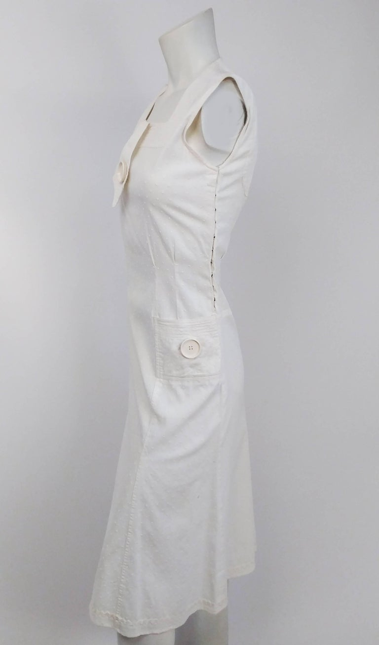 1920s White Swiss Dot Day Dress w/ Large Button Detail. Side snap closure. Faux neck tie detail w/ large button. Two square pockets with matching button details. Back cut-out detail. Rick rack trim on hem.