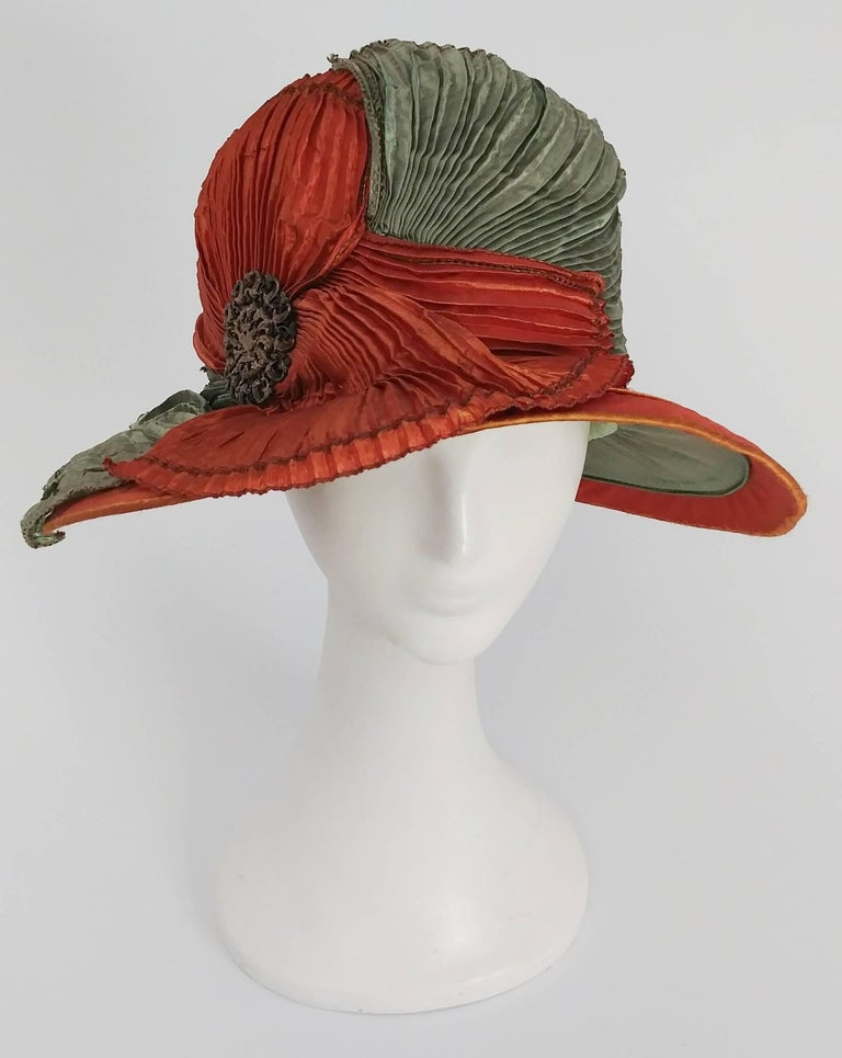 1920s Burnt Orange & Seafoam Green Wide Brim Cloche Hat. Pleated fabric drapes across the front of this hat, furthered embellished with art nouveau pin on side. Sits low over eyes for true 20s look.