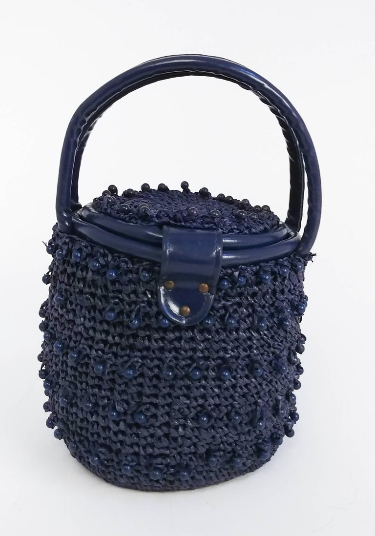 1960s Navy Raffia Woven Basket Purse. Wooden beads woven throughout. Leather straps, gold toned hardware. Clasp twists open and top flips up. Lined with cotton w/ one side inner pocket.