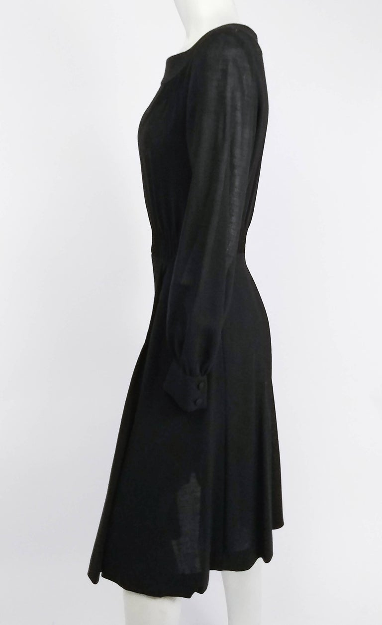 1960s Valentino Smocked Black Day Dress. 100% wool. Metal zipper closure at back. Bodice gathers at waistband, with smocking detail on front skirt.