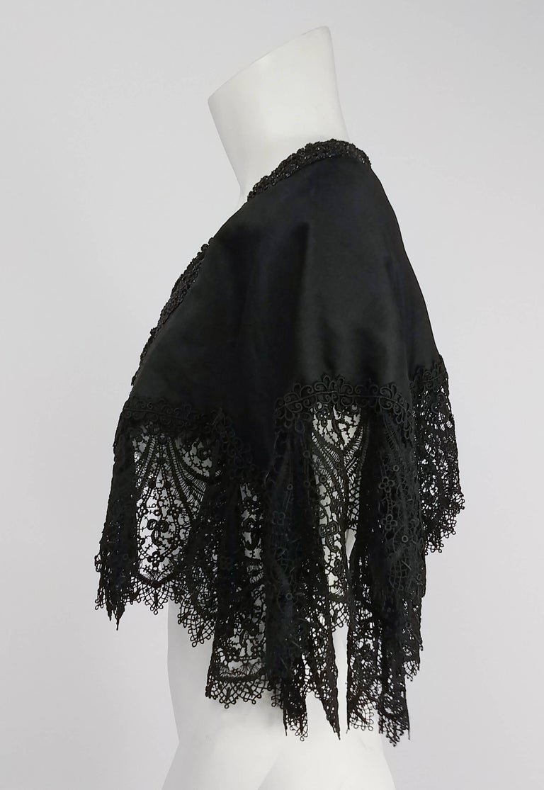 Victorian Black Beaded Battenburg Lace Mourning Capelet. Jet bead trim on collar and front opening. Hook and eye closures. Lined in satin.