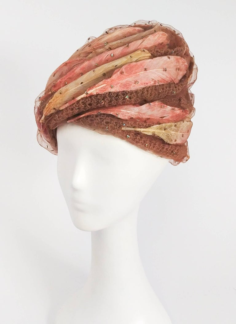 """1960s Christian Dior Tulle Turban w/ Feathers. Overlay of tulle fabric with glittery dots, draped in a swirled pattern over pink and peach feathers. 22"""" circumference."""
