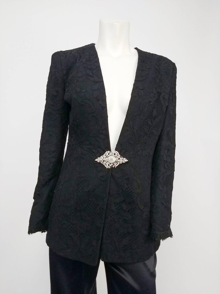 1980s Badgley Mischka Lace Blazer & Satin Trouser Pantsuit. Low cut collarless lace blazer fastens with rhinestone clasp at front. Padded shoulders. High waisted pleat front satin trousers.