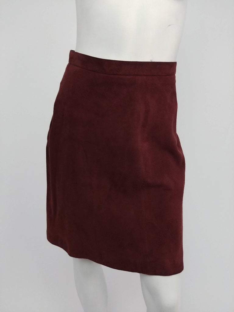 1990s Alaia Brown Vegan Suede Back Pleat Skirt. Brown suede skirt hits above the knee with A-line flare. All the details are at the back of the skirt, from flattering curved seam lines over to the bustle-like pleats. Zips up back and closes with a