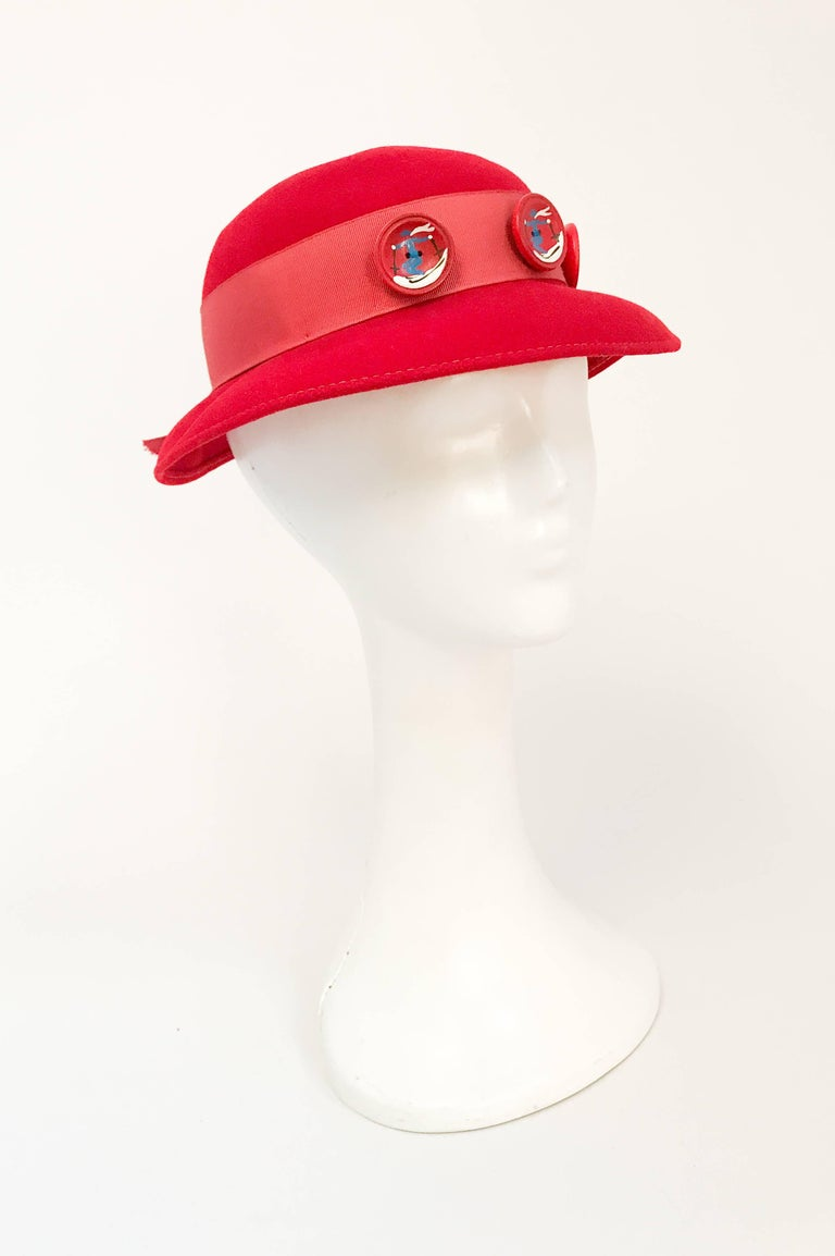 1930s Red Felt hat with Hand Painted Ski Buttons. Red felt hat with wide grosgrain band, back opening and Hand painted ski motif buttons.